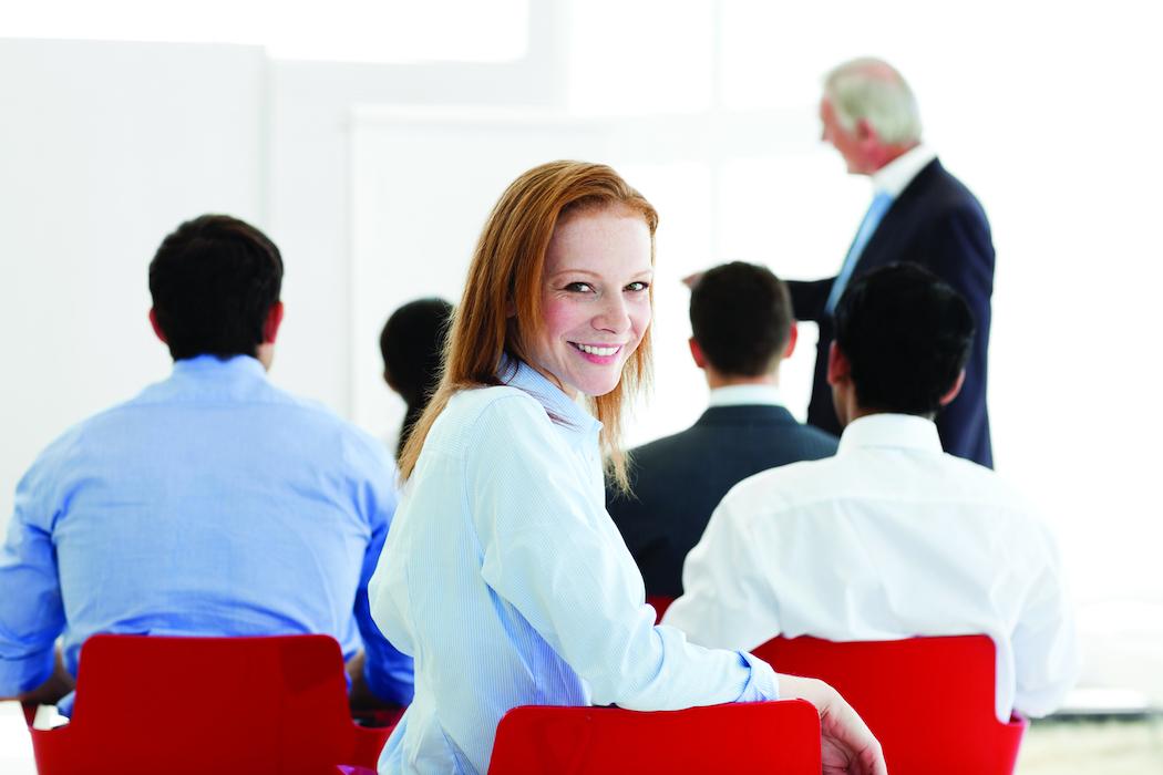 Lächelnde Frau als Zuhörerin bei Vortrag